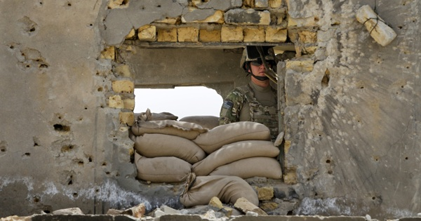 A U.S. Army soldier keeps a lookout from behind a bullet-riddled wall at Strongpoint Lugo in the village of Charqolba Olya in the Arghandab Valley